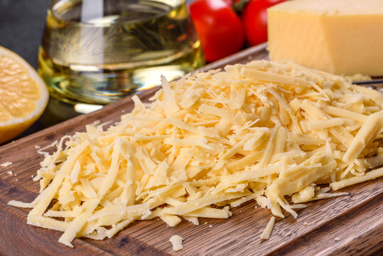 Fresh hard cheese grated on a large grater on a wooden cutting board