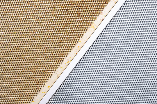 cleaning dirty clogged cooker hood filter from domestic kitchen. dirty and new clean filter. above view