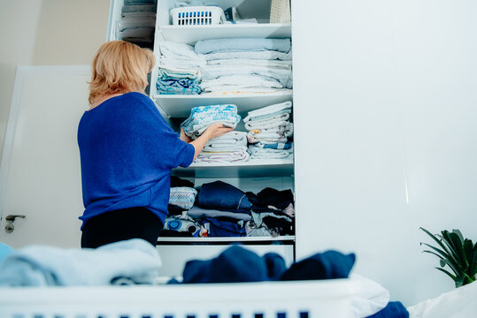 Back view of a woman organizing a wardrobe, holding towels in her hands and putting them on a shelf. Clean up your home space, make your home cozy. Selective focus, copy space.