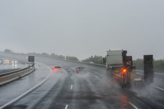 A truck and several cars driving down the highway on a day complicated by the rain.