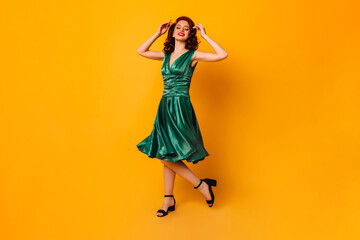 Enthusiastic ginger woman dancing on yellow background. Full length view of stunning young lady in...