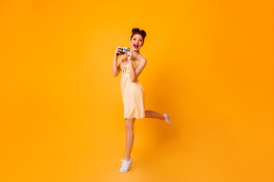 Emotional pinup girl with camera dancing on yellow background. Studio shot of female photographer in dress.