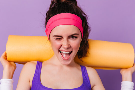 Energetic dark-haired girl in purple sports top and bright headband winks while holding yoga mat