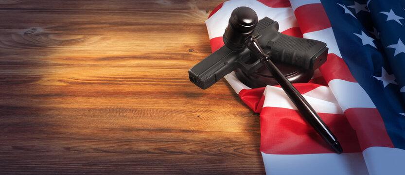 Judge gavel and gun on USA flag. Gun law concept