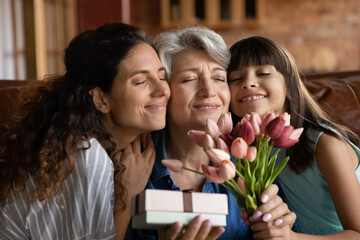 Close up happy three generations of women celebrating event, touching cheeks, cute little girl with...
