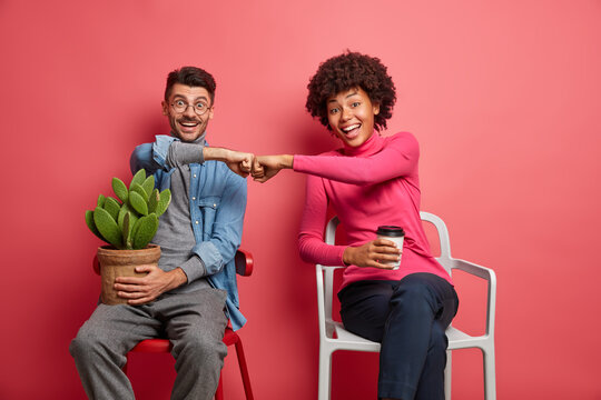Cheerful mixed race couple make fist bumps after succesful finishing of common task pose on comfortable chairs drink takeaway coffee hold potted cactus have happy expressions. We did it together