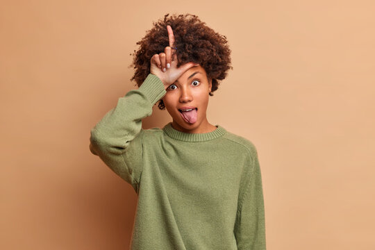 Funny curly haired young African American woman makes loser gesture sticks out tongue dressed in casual jumper isolated over brown background mocks at someone who lost bet. Body language concept