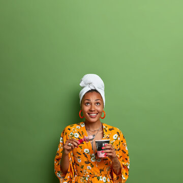 Vertical shot of happy dark skinned Afro American woman eats cold ice cream enjoys spending time at home dressed in casual clothes isolated over green background with copy space. Summer dessert