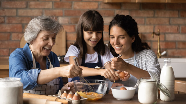 Happy little girl with smiling young mother and mature grandmother preparing dough close up, stirring fresh eggs with whisk, sitting at table in modern kitchen, family enjoying leisure time together