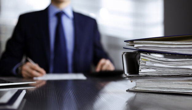 Binders with papers are waiting to be processed by man accountant in blue blazer staying at home during covid pandemic. Taxes and audit concept. Internal Revenue Service inspector checking financial
