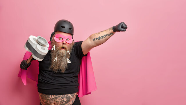 Surprised bearded man keeps mouth widely opened stretches tattooed arm holds tool for cleaning pretends to be superhero ready for actions isolated over pink background with copy space aside.