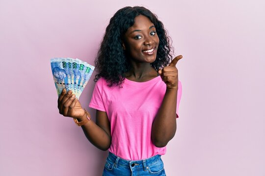 Beautiful african young woman holding south african 100 rand banknotes smiling happy pointing with hand and finger to the side