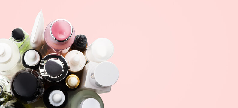 Many cosmetics tubes top view banner on  pink background, copy space.