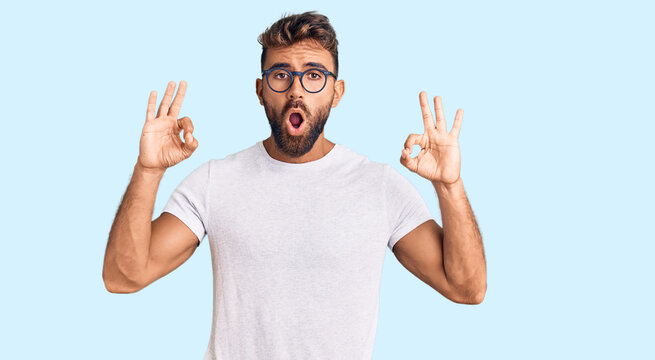 Young hispanic man wearing casual clothes and glasses looking surprised and shocked doing ok approval symbol with fingers. crazy expression