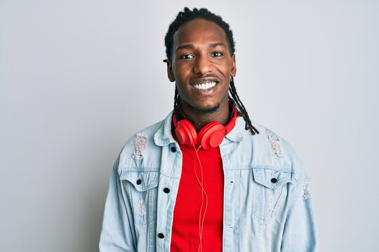 African american man with braids listening to music using headphones looking positive and happy standing and smiling with a confident smile showing teeth