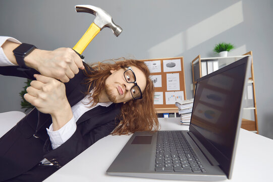 Computer failure, error, stress at work concept. Mad aggressive impulsive crazy adult guy breaks down laptop device screen with hammer. Funny angry nervous office worker smashing monitor and keyboard