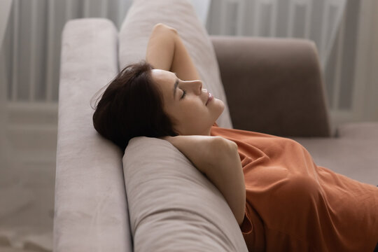 Close up peaceful satisfied young woman leaning back with hands behind head on cozy couch at home, attractive calm tranquil female taking nap, stretching and daydreaming on comfortable sofa
