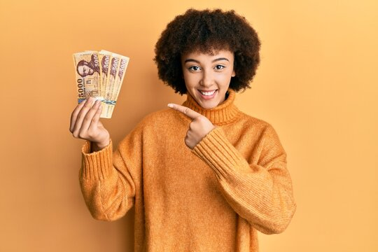 Young hispanic girl holding 5000 hungarian forint banknotes smiling happy pointing with hand and finger