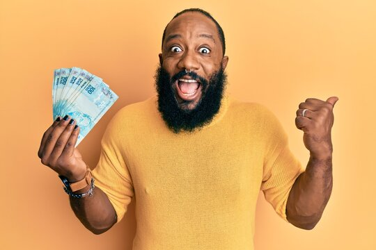 Young african american man holding 100 brazilian real banknotes pointing thumb up to the side smiling happy with open mouth
