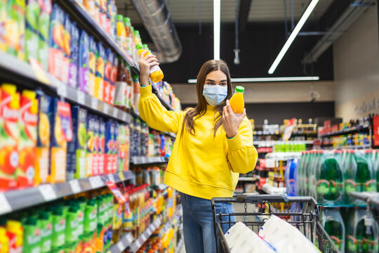 Young person with protective face mask buying groceries supplies in the supermarket. Preparation for a pandemic quarantine due to coronavirus covid-19 outbreak.