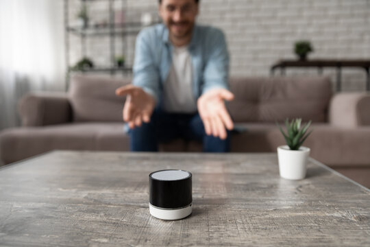 Close up man talking to wireless smart speaker, sitting on couch at home, guy activating digital assistant, asking question to electronic device, searching in internet, listening to music