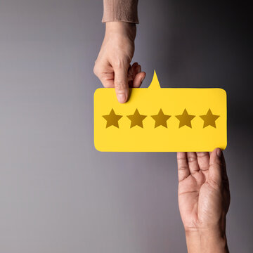 Customer Experience Concept, Happy Client giving Five Star Rating Feedback on Card to a Businessman. Top View