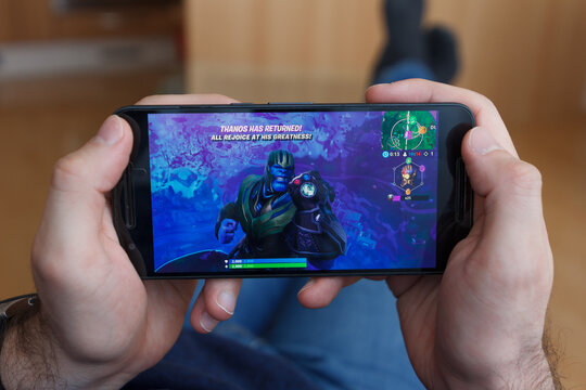 LOS ANGELES, CALIFORNIA - JUNE 3, 2019: Lying Man holding a smartphone and playing the Fortnite Avengers: Endgame game on the smartphone screen. An illustrative editorial image.