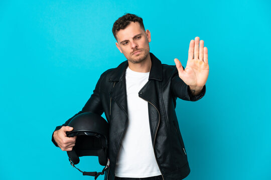 Caucasian man with a motorcycle helmet isolated on blue background making stop gesture and disappointed