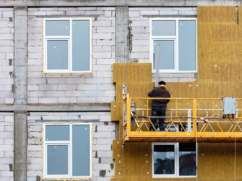 The builder stands on a suspended cradle and insulates the facade of the house under construction with mineral insulation.