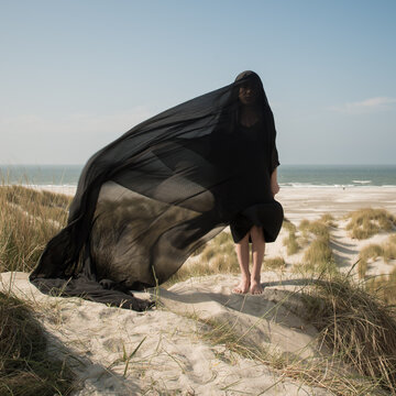Conceptual fineart portrait of a girl wrapped in thin black drape blwoing in the wind on dunes near ocean