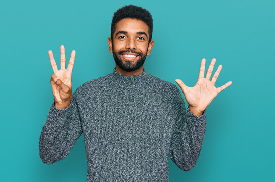 Young african american man wearing casual clothes showing and pointing up with fingers number eight while smiling confident and happy.
