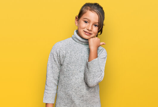 Little beautiful girl wearing casual turtleneck sweater smiling with happy face looking and pointing to the side with thumb up.