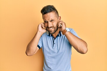 Fototapeta Handsome man with beard wearing casual clothes covering ears with fingers with annoyed expression for the noise of loud music. deaf concept. obraz