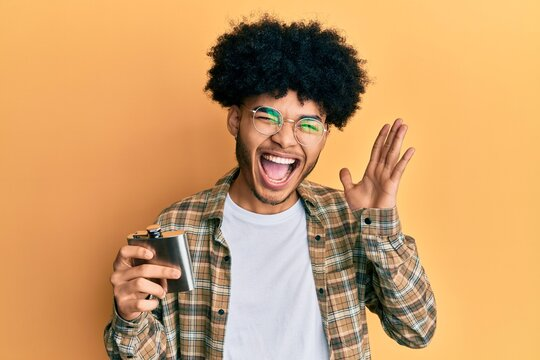 Young african american man with afro hair drinking alcohol from whiskey flask screaming proud, celebrating victory and success very excited with raised arms