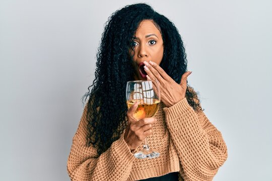 Middle age african american woman drinking a glass of white wine covering mouth with hand, shocked and afraid for mistake. surprised expression