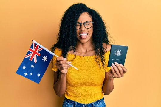 Middle age african american woman holding australian flag and passport sticking tongue out happy with funny expression.