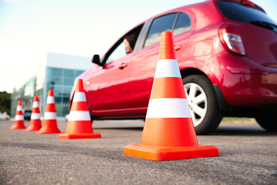 Traffic cones near red car outdoors. Driving school exam