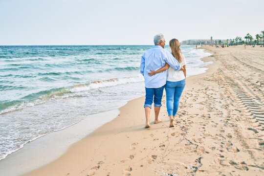 Middle age hispanic couple hugging walking at the beach.