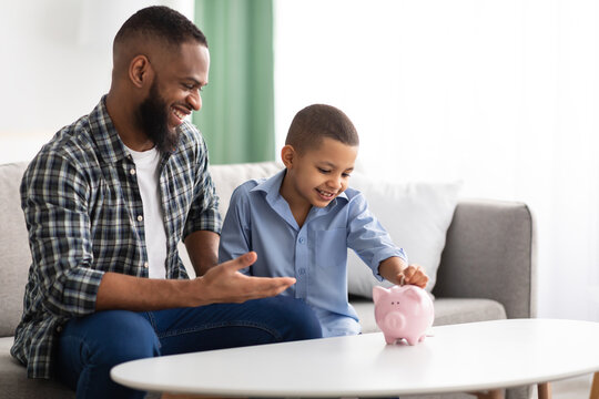 African Father And Son Putting Personal Savings In Piggybank Indoor