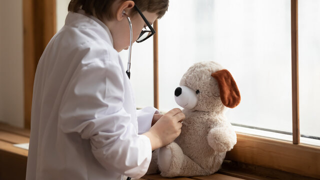Caring small boy child in white medical uniform hold stethoscope play hospital game examine fluffy toy bear. Little 7s kid act as doctor cure stuffed animal dream of future medicine clinic career.