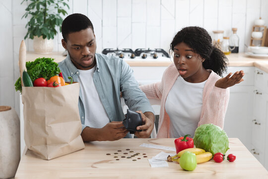 Frustrated African American Couple In Kitchen Counting Remaining Money After Food Shopping