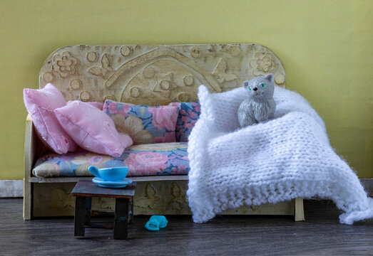 Dollhouse daybed with a toy cat and a cup of tea.