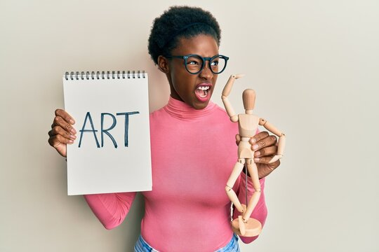 Young african american girl holding wooden manikin and art word on notebook angry and mad screaming frustrated and furious, shouting with anger. rage and aggressive concept.