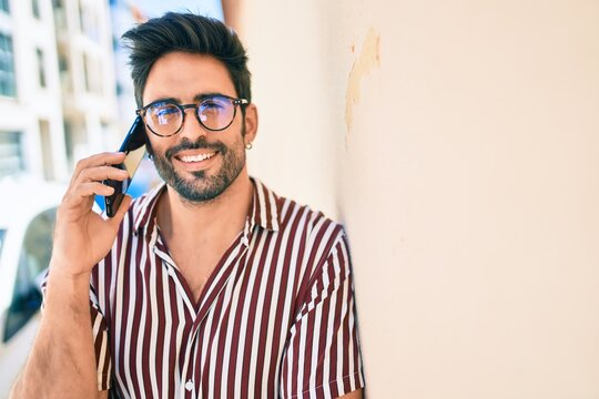 Young handsome hispanic man with beard smiling happy outdoors speaking on the phone