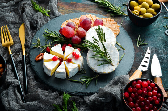 Camembert cheese. Brie cheese with cranberries and snacks. Rustic style. Free copy space.
