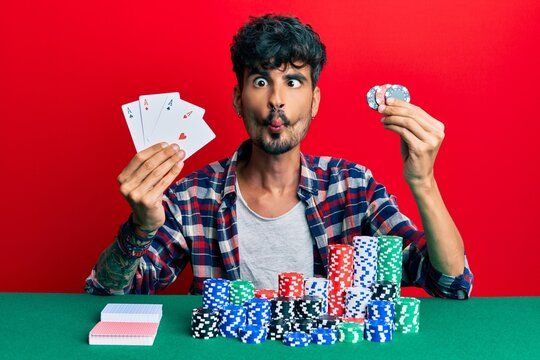 Young hispanic man playing poker holding cards and casino chips making fish face with mouth and squinting eyes, crazy and comical.