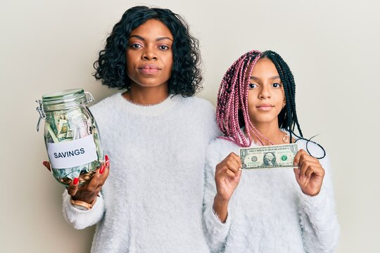 Beautiful african american mother and daughter holding jar with savings and 1 dollar banknote relaxed with serious expression on face. simple and natural looking at the camera.