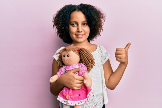 Young little girl with afro hair holding animal doll toy smiling happy and positive, thumb up doing excellent and approval sign