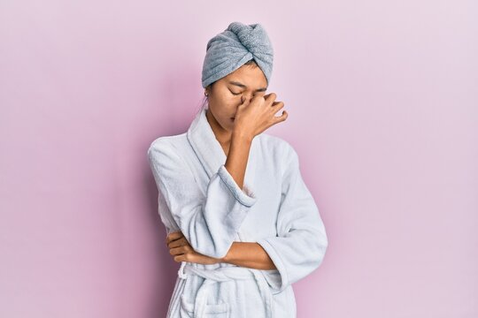 Young chinese woman wearing shower towel cap and bathrobe tired rubbing nose and eyes feeling fatigue and headache. stress and frustration concept.