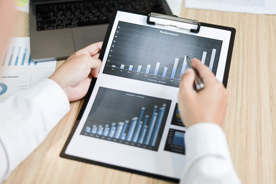 Manager holds company earnings report documents, Manager is checking the information in the report, documentation is a bar chart, business administration concept.